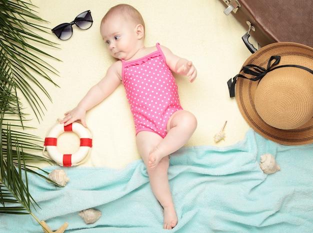 Mignonne petite fille avec des accessoires de plage sur la lumière. vacances en mer avec bébé
