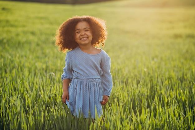 Mignonne petite fille africaine sur le terrain au coucher du soleil