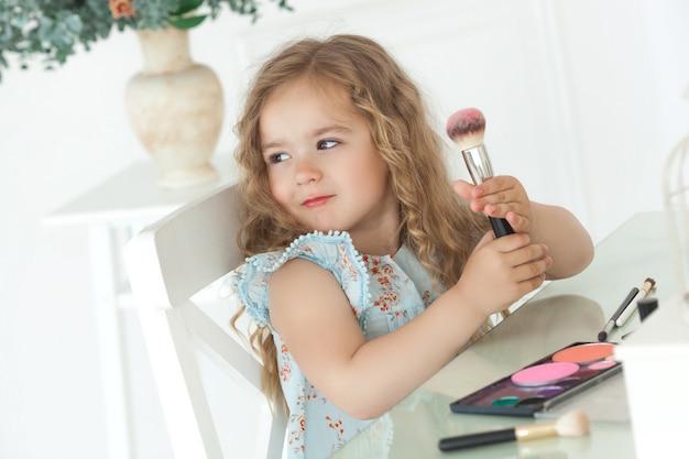 Mignonne petite fille appliquant maquillage regardant dans le miroir. petite fille fashionista jouant avec les cosmétiques de sa mère. adorable enfant à l'intérieur