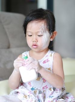 Mignonne petite fille appliquant la poudre pour bébé sur son visage et sa main.