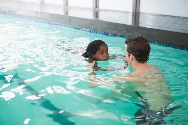 Mignonne petite fille apprend à nager avec l'entraîneur