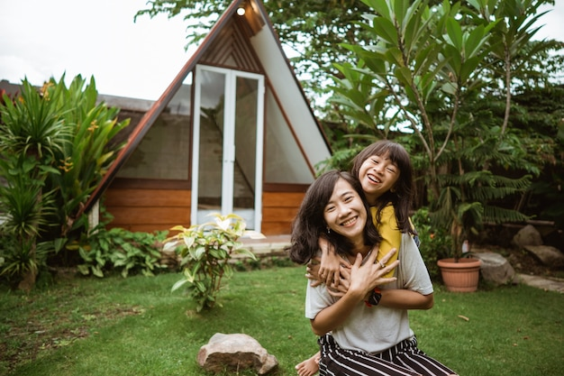 Mignonne petite fille asiatique aidant sa mère à jouer et s'amuser dans une arrière-cour.