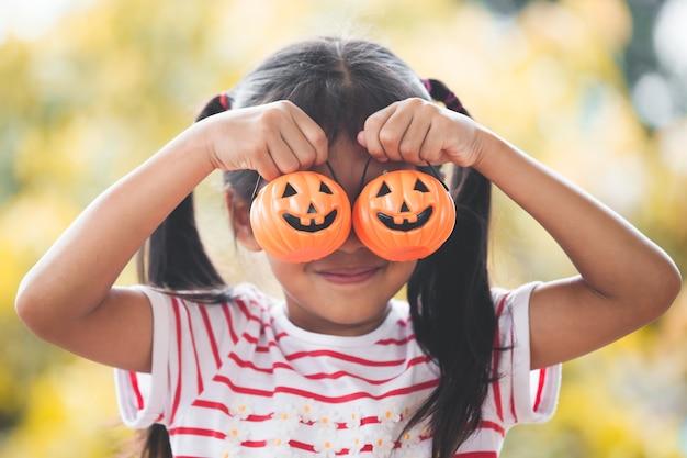 Mignonne petite fille asiatique avec citrouille seau. funny kid pour la fête d'halloween.