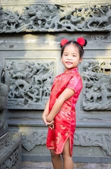 Mignonne petite fille asiatique en costume traditionnel chinois souriant et debout dans le temple.