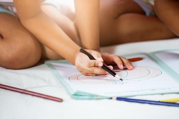 Mignonne petite fille asiatique dessine avec ses crayons. tonalité de couleur vintage. fermer
