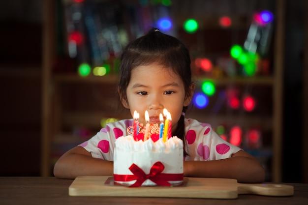 Mignonne petite fille asiatique avec un gâteau d'anniversaire dans la fête d'anniversaire dans le ton sombre