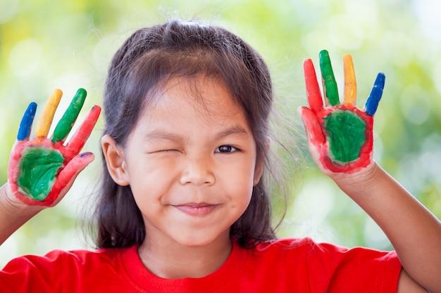 Mignonne petite fille asiatique avec des mains peintes souriant avec plaisir et bonheur