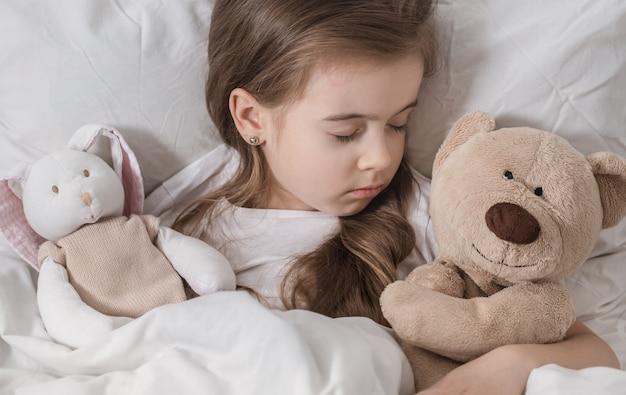 Mignonne petite fille au lit avec peluche.