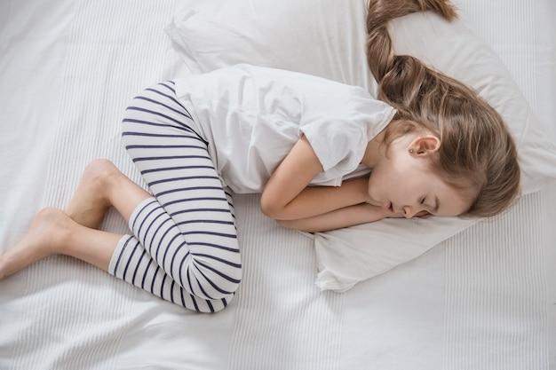 Mignonne petite fille aux cheveux longs qui dort dans son lit.