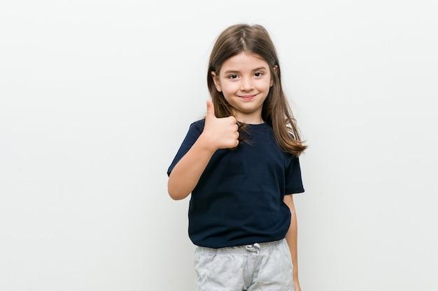 Mignonne petite fille caucasienne souriant et levant le pouce vers le haut