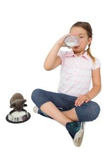 Mignonne petite fille et chaton gris tous les deux boire du lait