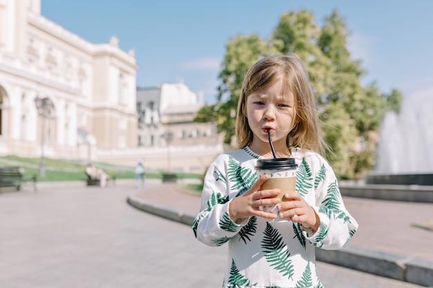 Mignonne petite fille ciblée en robe d'été, boire du cacao à l'extérieur au soleil