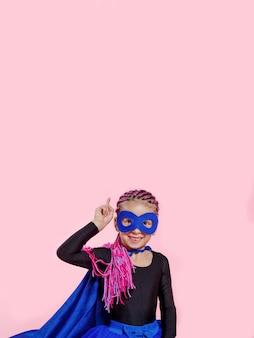 Mignonne petite fille en costume de super-héros tenant sa main et pointant vers le haut sur l'espace rose. copiez l'espace.