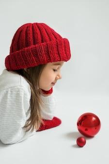 Mignonne petite fille dans un chapeau rouge avec des décorations de noël sur fond blanc.
