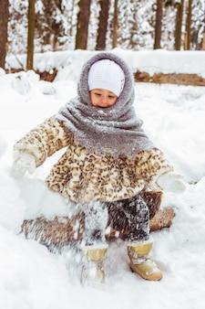 Mignonne petite fille dans des vêtements chauds en hiver