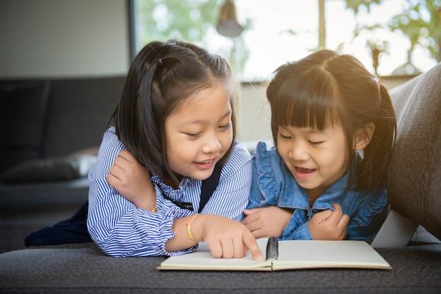 Mignonne petite fille dans des vêtements décontractés lisant un livre et souriant en position couchée sur un canapé dans la chambre.