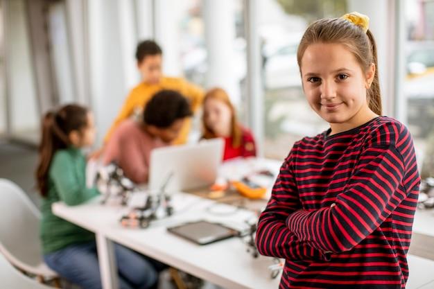 Mignonne petite fille debout devant un groupe d'enfants programmant des jouets électriques et des robots en classe de robotique