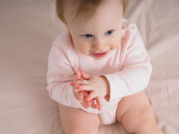 Mignonne petite fille douce, 10 mois, assise sur le lit, frappant dans ses mains, souriante, en gros plan. portrait d'une jeune fille dans les tons roses. concept de produits pour bébé.