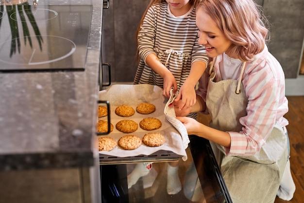 Mignonne petite fille enfant aider maman à cuire des biscuits dans un four de cuisine