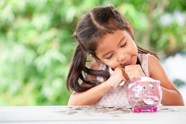 Mignonne petite fille enfant asiatique avare son argent et économiser de l'argent dans la tirelire pour l'avenir