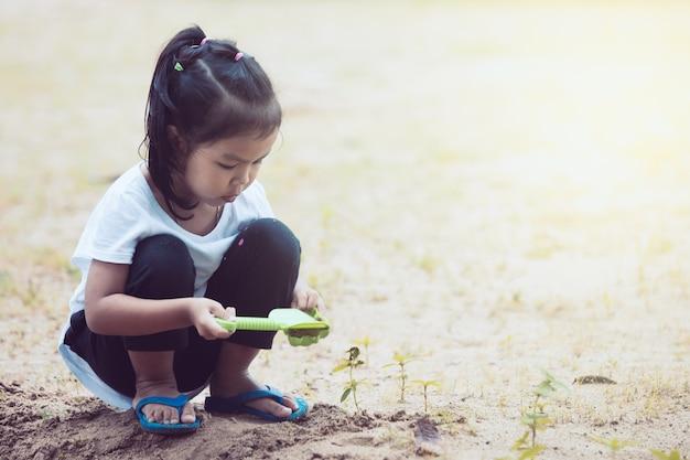 Mignonne petite fille enfant asiatique s'amuser à jouer avec du sable dans la cour de récréation