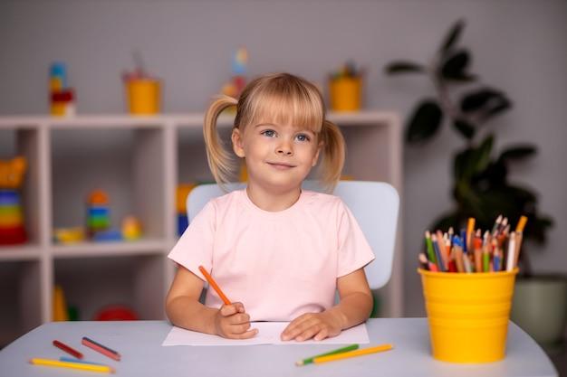 Mignonne petite fille enfant écrit avec des crayons en garderie