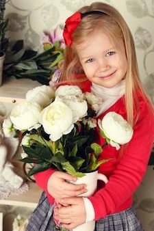 Mignonne petite fille enfant avec des fleurs de printemps, heureuse petite fille avec panier de fleurs.