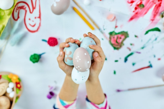 Mignonne petite fille enfant le jour de pâques tenir l'oeuf de pâques dans la main. fille avec des oeufs peints sur fond clair. vue de dessus, joyeuses pâques