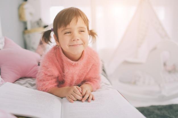 Mignonne petite fille enfant lit un livre à la maison. drôle bel enfant s'amusant dans la chambre d'enfant.