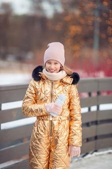 Mignonne petite fille enfant va patiner à l'extérieur.