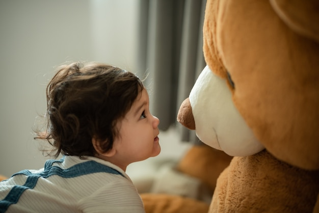 Mignonne petite fille enjouée apprenant à marcher et à se tenir debout en prenant appui sur un canapé à la maison tout en détournant les yeux avec malice