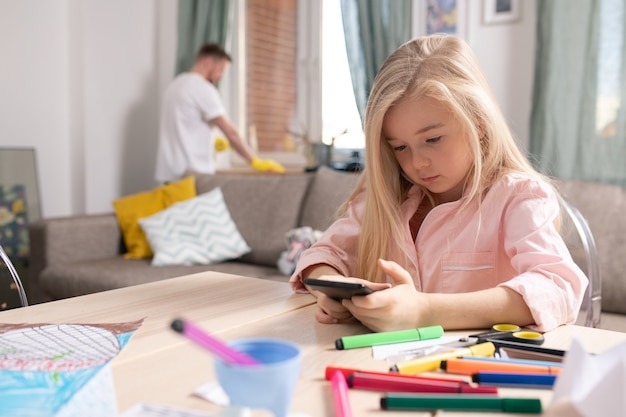 Mignonne petite fille faisant défiler les photos dans le smartphone alors qu'il était assis par table dans le salon sur fond de son père faisant les tâches domestiques