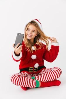 Mignonne petite fille gaie portant le costume de noël isolé, tenant un téléphone portable, prenant un selfie