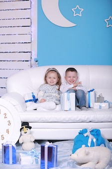 Mignonne petite fille et garçon avec des coffrets cadeaux assis sur un canapé blanc. célébrant noël et le nouvel an.