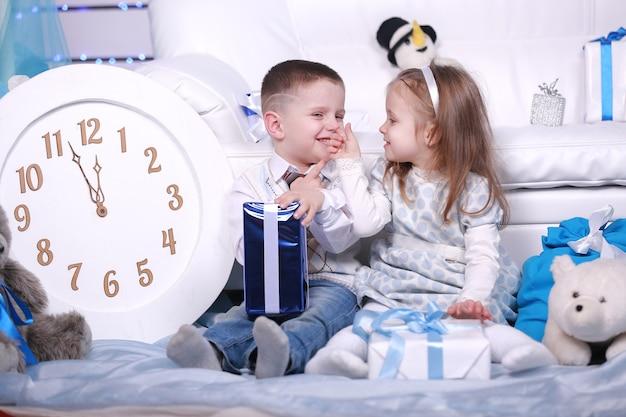 Mignonne petite fille et garçon avec des coffrets cadeaux et grande horloge blanche assis près du canapé blanc à noël et nouvel an