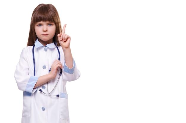 Mignonne petite fille grave médecin portant l'uniforme tient le stéthoscope et montre le geste du doigt sur fond blanc isolé