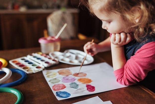 Mignonne petite fille heureuse, adorable enfant d'âge préscolaire, peinture avec de l'eau