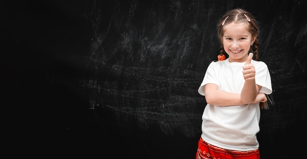 Mignonne petite fille heureuse avec les pouces vers le haut sur le fond de la commission scolaire