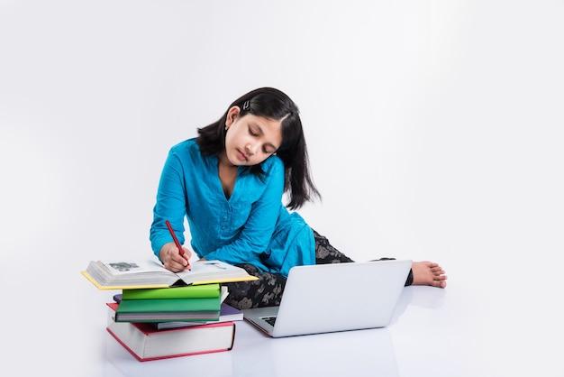 Mignonne petite fille indienne ou asiatique étudiant sur un ordinateur portable ou travaillant sur un projet scolaire en position couchée ou assise sur le sol, isolée sur fond blanc