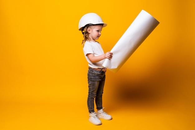 Mignonne petite fille ingénieur avec casque tenant bluepring isolé sur mur jaune