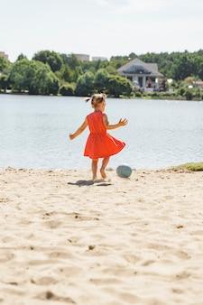 Mignonne petite fille jouant avec un ballon sur la plage, sport d'été pour enfants à l'extérieur.