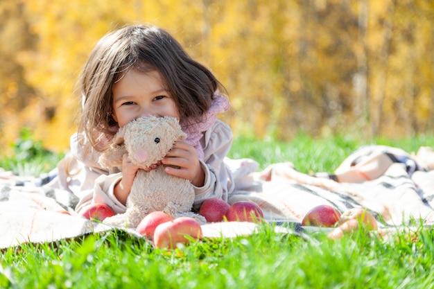 Mignonne petite fille jouer avec des jouets sur pique-nique d'automne