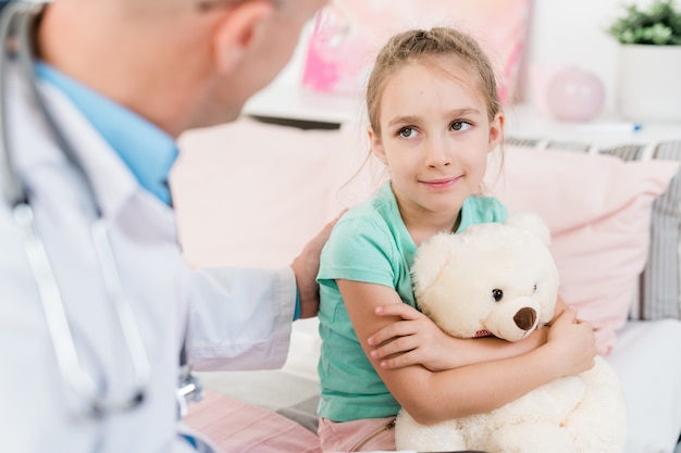 Mignonne petite fille avec jouet moelleux en regardant son médecin avec le sourire tout en écoutant ses conseils en cabinet médical