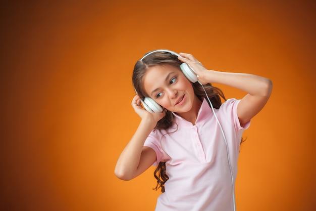 La mignonne petite fille joyeuse avec un casque sur le mur orange