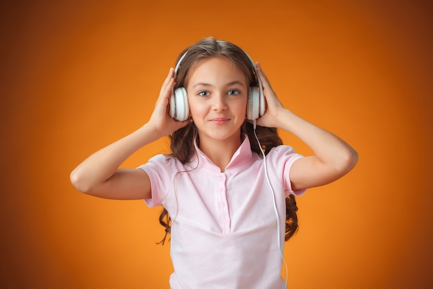La mignonne petite fille joyeuse sur le mur orange