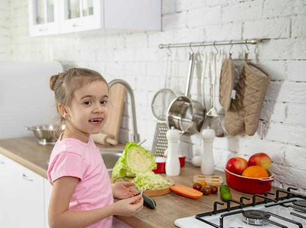Mignonne petite fille avec des légumes dans la cuisine. le concept d'une alimentation et d'un mode de vie sains. valeur familiale.