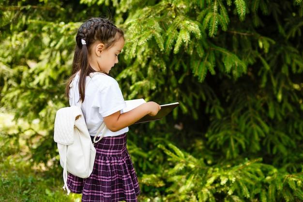 Mignonne petite fille lisant un livre dehors sur l'herbe