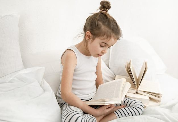 Mignonne petite fille lisant un livre sur le lit dans la chambre.