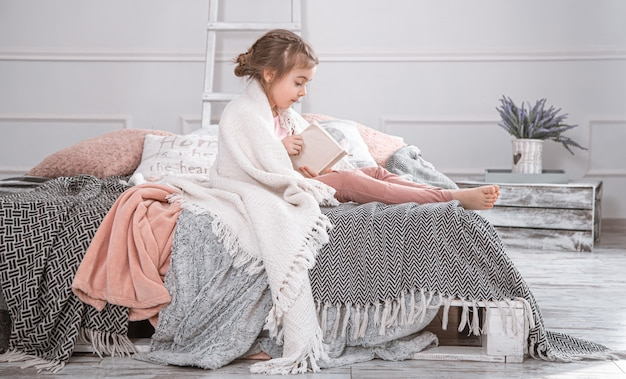 Mignonne petite fille lisant un livre sur le lit.