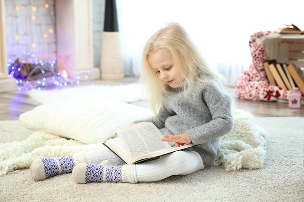 Mignonne petite fille lisant un livre à la maison